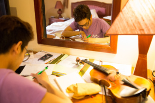 Anousone Pranikay from Lao is composing music in his room during the workshop. He majors violin atLao National Sch